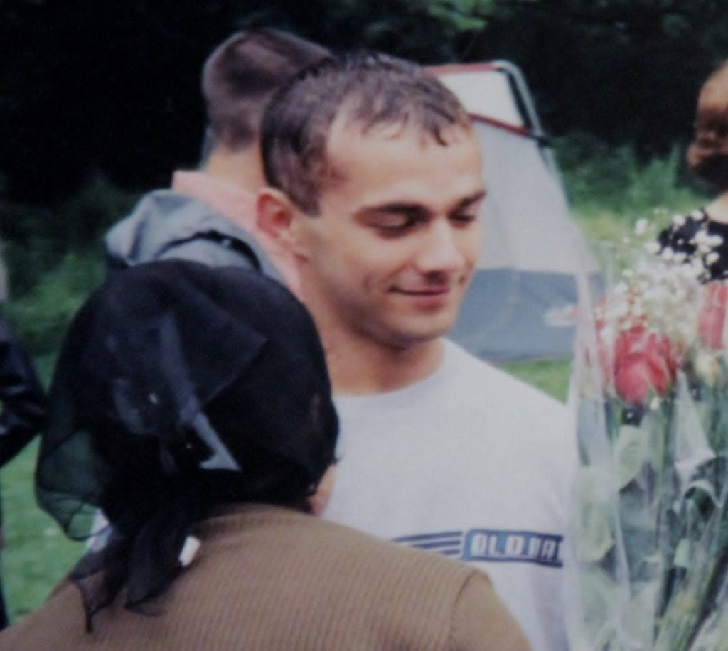 Ivan Teleguz holding flowers at his sister's baptism.
