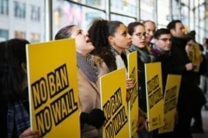 Amnesty International USA activists speak out against a ban and a wall against people