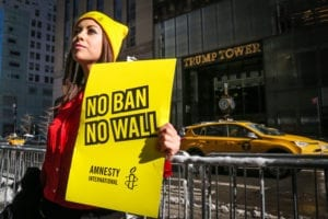 "A wona protester holding a ""No Ban No Wall"" sign in front of Trump Tower"
