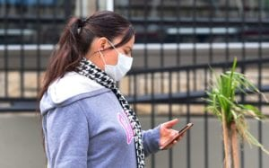 Woman wearing a facemark during COVID-19 pandemic looks at the cell phone in her hand