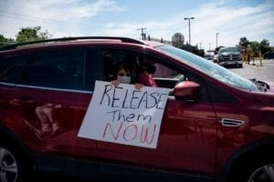 "Woman in car with masks holds sign reading ""Release them NOW"""