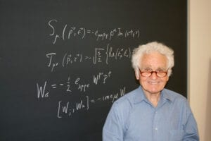 Person smiling standing in front of chalk board with equations