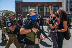 Women stand in the street unarmed as right-wing protesters stand across them, armed