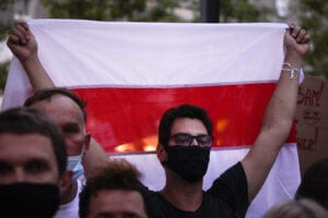 Young man holds flag while wearing a mask